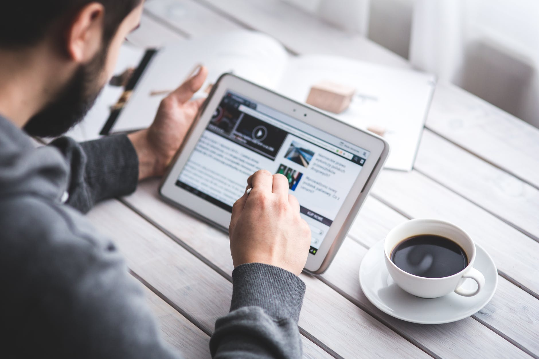 man sitting at a desk looking at ipad, a cup of black coffee next to him - cryptocurrency simplified