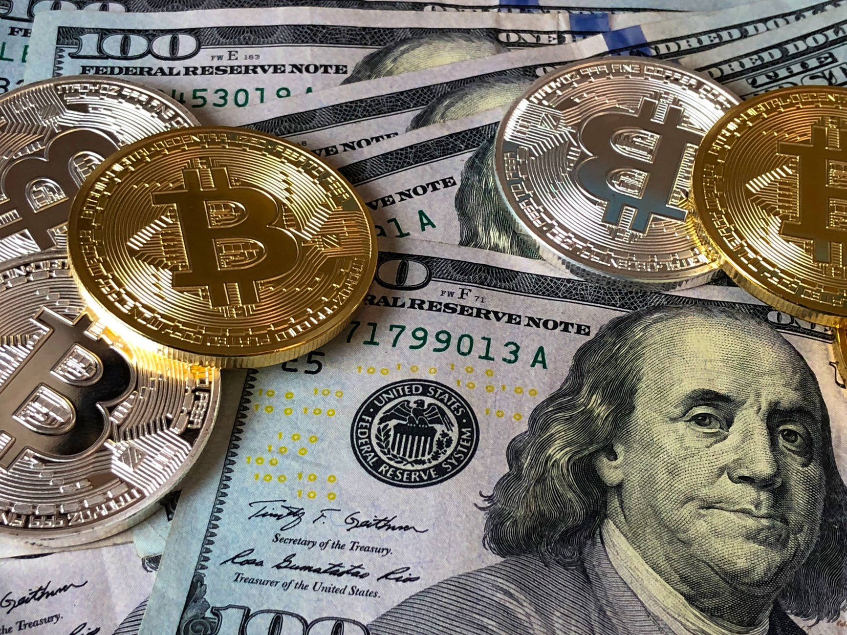 currency notes and coins with symbol B on display - cryptocurrency simplified