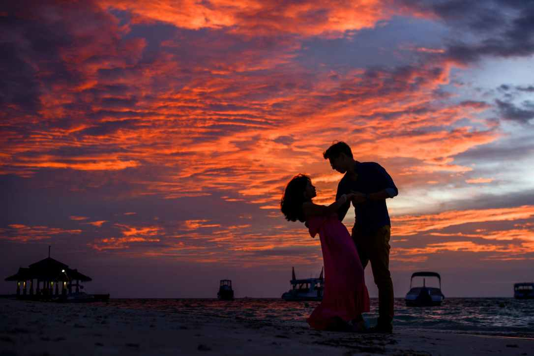 a young couple dance under the setting sun with a colorful orange-grey sky in the background
