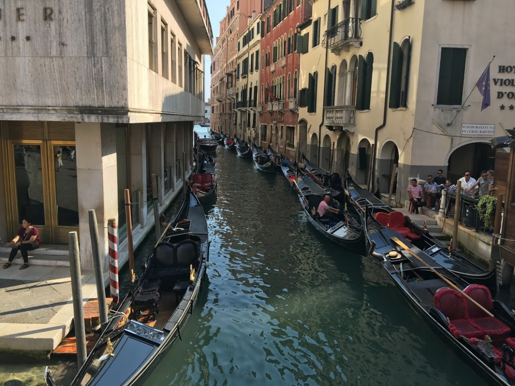 Gondolas parked on both sides of a small canal in Venice