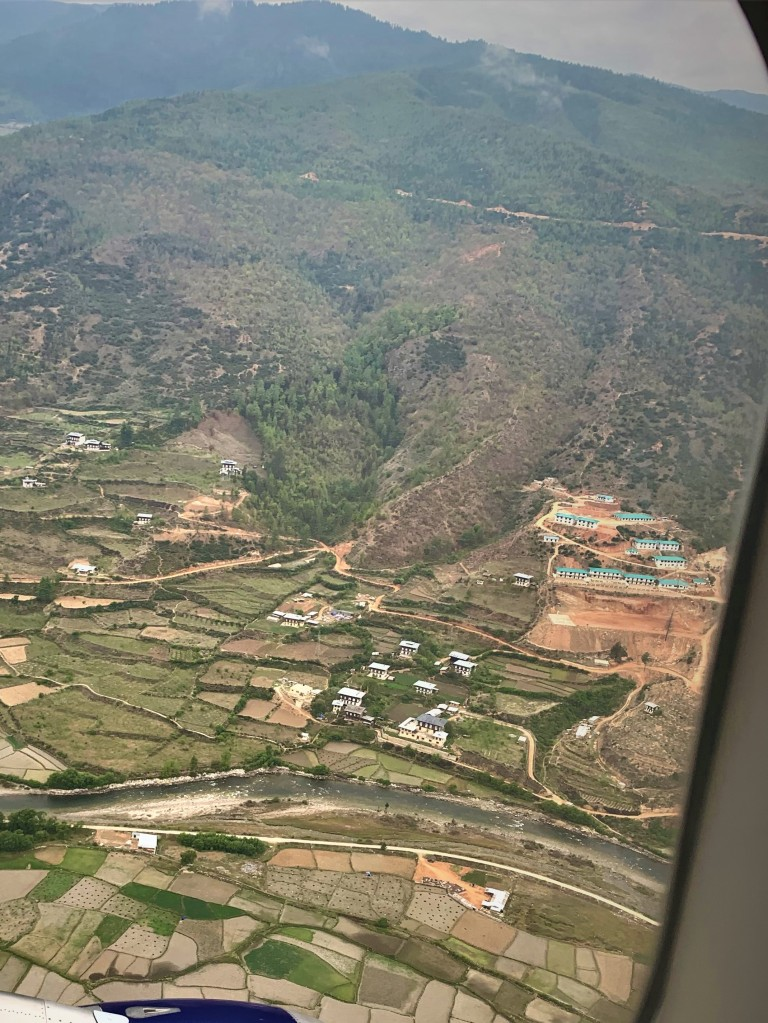 a view of houses and settlements in a valley in the Himalayas from a airplane window on the way to Paro International airport from Delhi