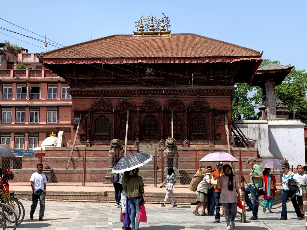 Durbar square with many tourists, sunny day so many people carry umbrellas