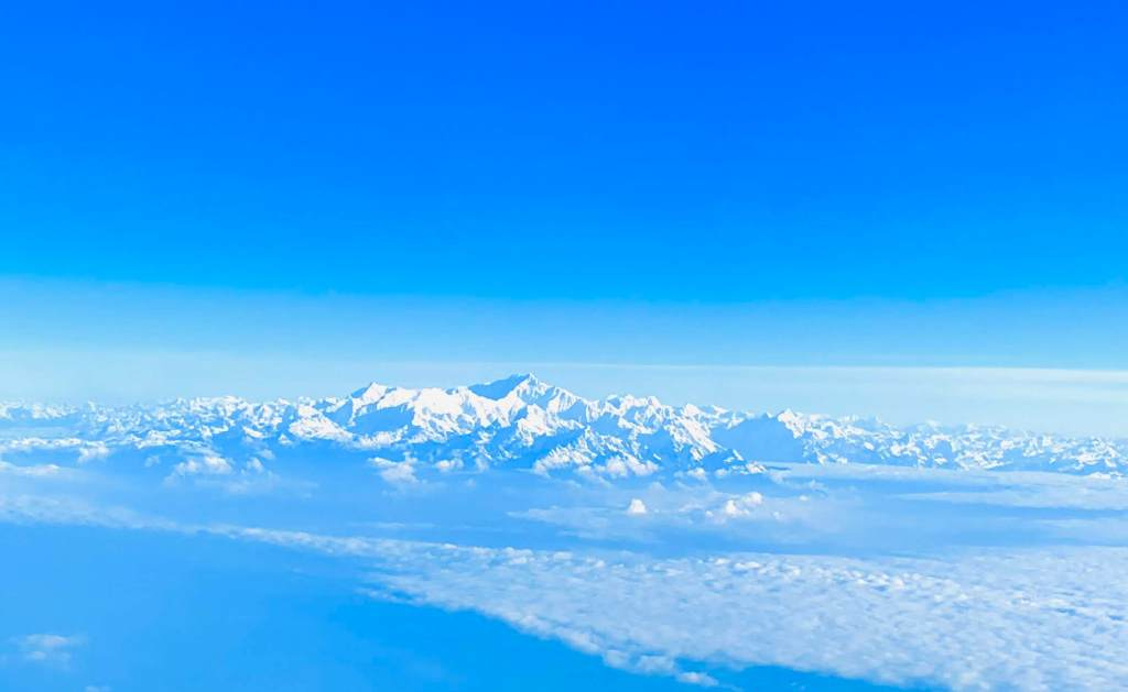 The Himalayan range of mountains seen from a plane above the cloud line.