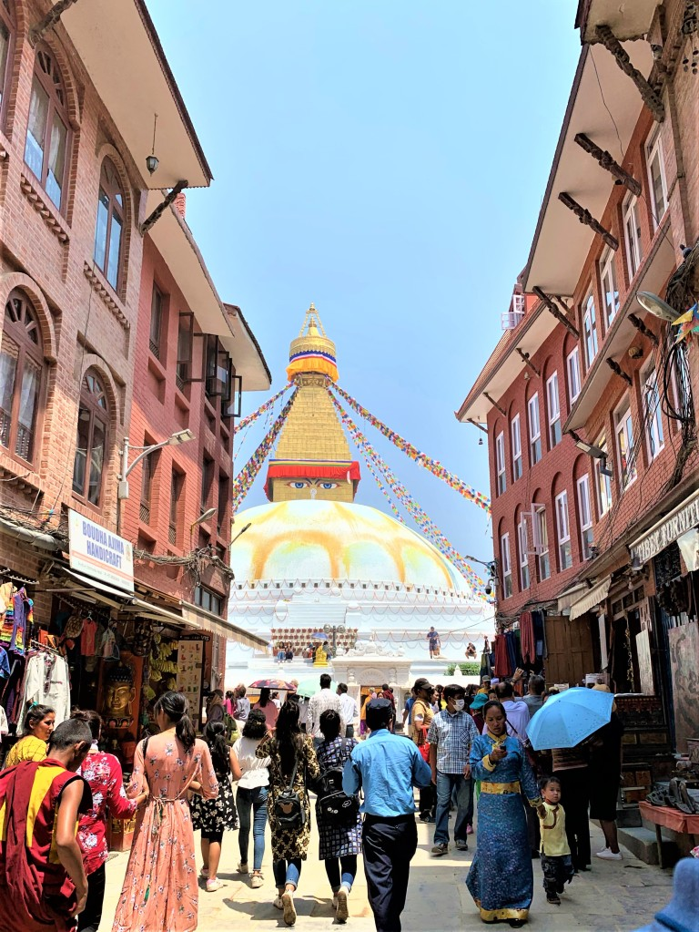 The way to the Boudhanath Stupa, you can see the Stupa and there are a lot of people walking towards the center.