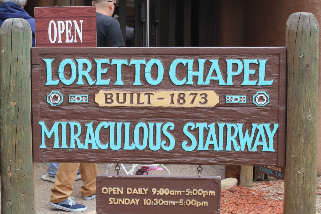 A sign board that says Loretto Chapel Miraculous Stairway