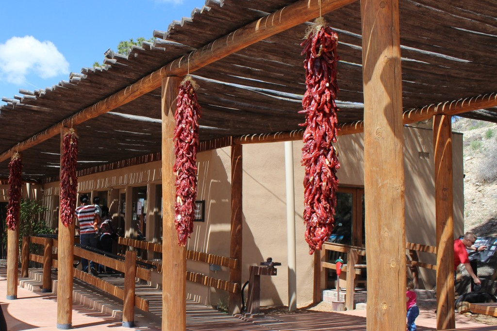 Stucco building in Santa Fe, with bunches of red chilies hanging in the front.