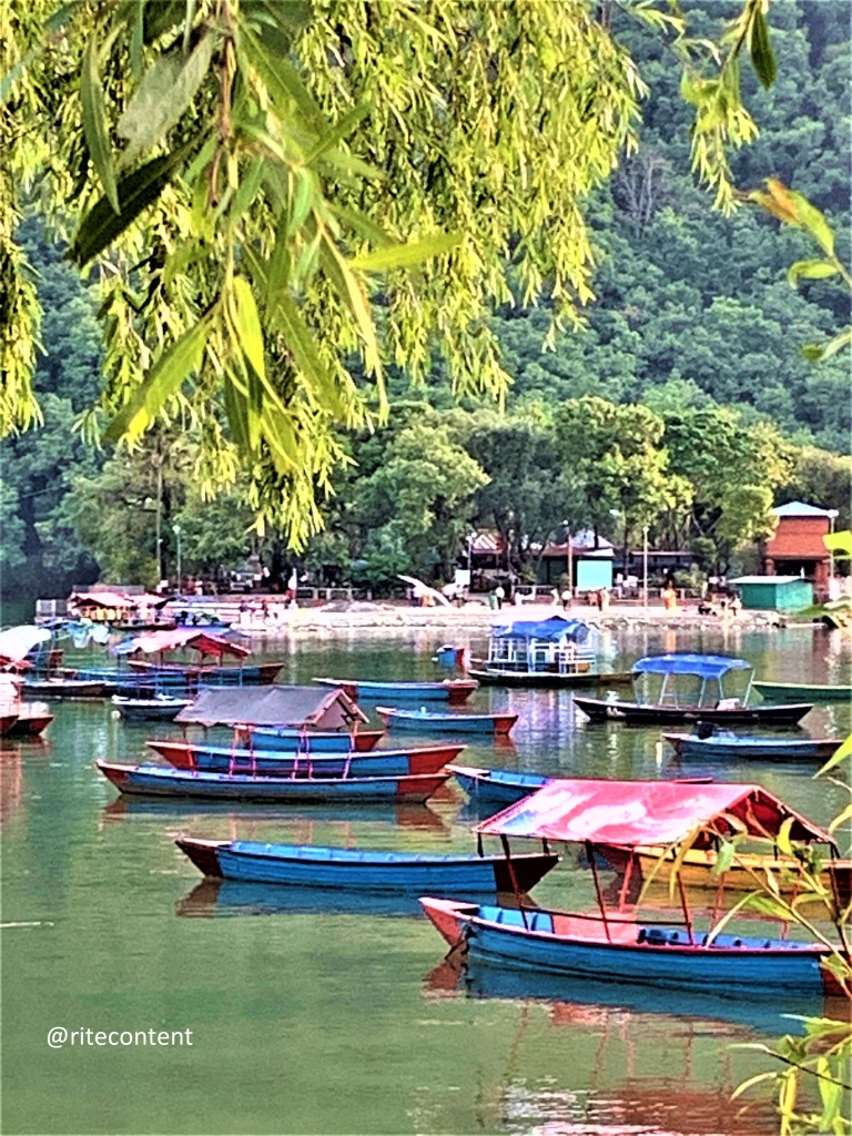 Veiw of Phewa lake in Pokhara. Places to see in Nepal. Boats rest on the water.