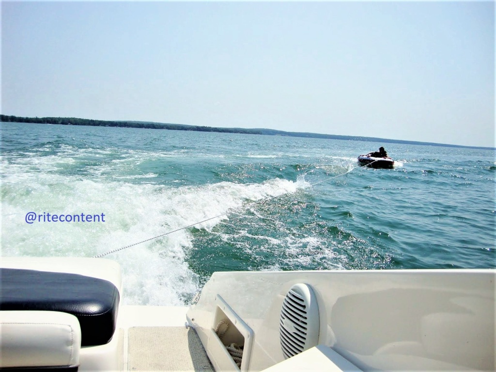 Motor boat driving fast on lake burt with a raft tied behind dragging rider