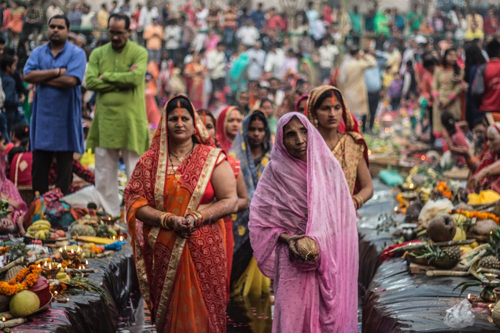 Women walk through a market, one woman is dressed as a widow