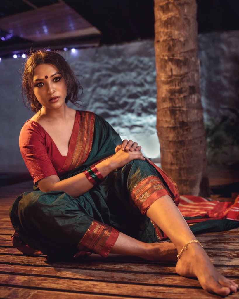 A woman in sari sitting on the floor looking sad