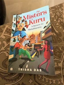 the book The Misters Kuru on a couch