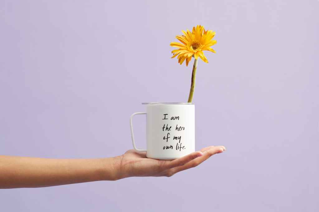 a hand holding a mug that says I am the hero of my life and has a yellow flower in it. how to market your blog