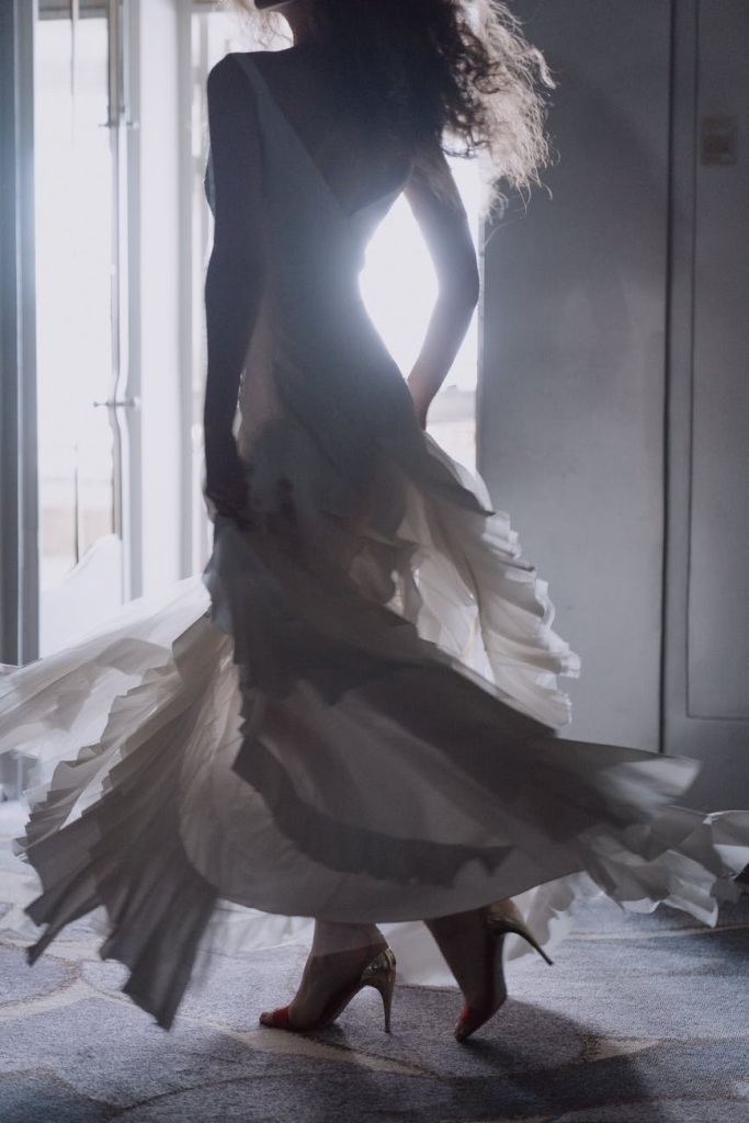 a lady in a white flowing full length dress, twirling around with the sunlit window silhouetting her.